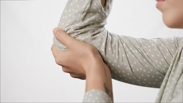 Dor no cotovelo, mão feminina tocando o cotovelo no fundo branco, close-up