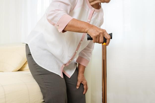 Dor no joelho da mulher sênior com vara, problema de saúde do conceito sênior