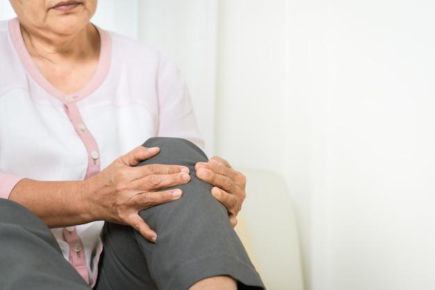 Dor no joelho da mulher sênior em casa, problema de saúde do conceito sênior