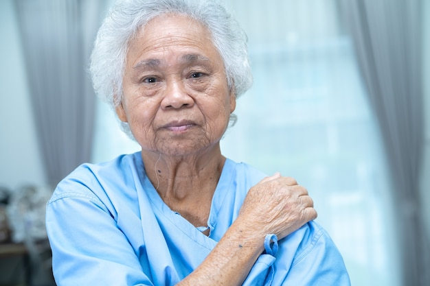 Dor no ombro da mulher idosa ou idosa asiática na enfermaria do hospital: conceito médico forte e saudável