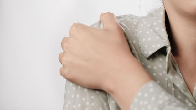 Dor no ombro, mão feminina tocando o ombro em fundo branco closeup