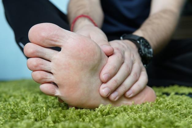Dor no pé. massagem nos pés masculinos. pedicuras. pé quebrado, um pé dolorido, massageando o calcanhar.