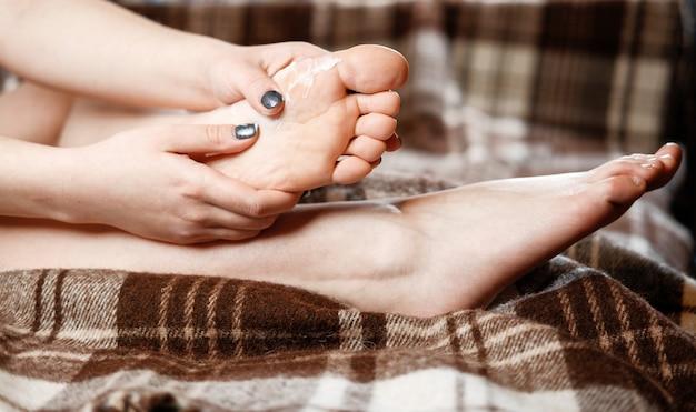 Dor no pé, menina coloca as mãos nos pés, massagem nos pés, cãibras, espasmo muscular, esfregue o creme no pé, close-up