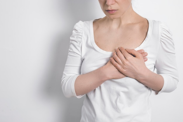 Dor no peito de uma mulher. coração preocupado. câncer mamário.