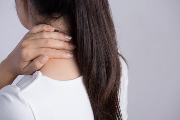 Dor no pescoço e no ombro da mulher do close up e ferimento. conceito de cuidados de sa