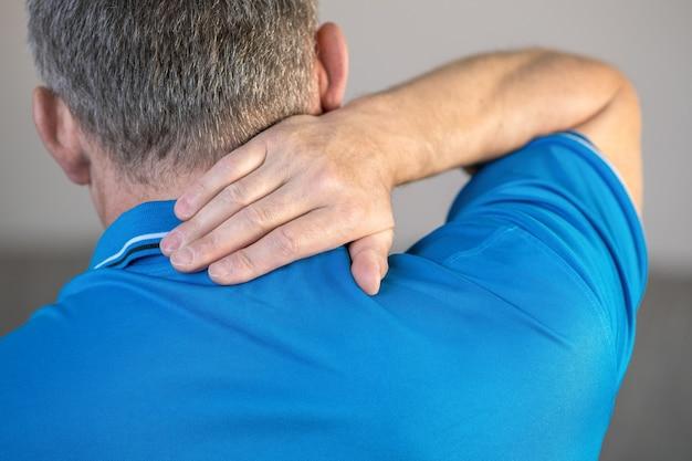 Dor no pescoço, o homem massageia o local da inflamação com a mão.