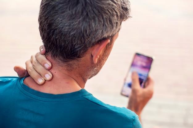 Dor no pescoço usando smartphone ao ar livre. conceito de saúde, estilo de vida e tecnologia