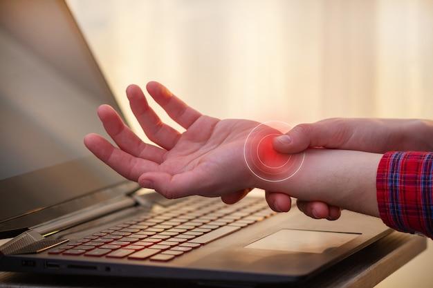 Dor no pulso por causa do longo trabalho no laptop. síndrome do túnel. doença profissional e dor nas mãos