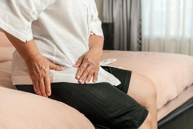 Dor no quadril da mulher idosa em casa, problema de saúde do conceito sênior