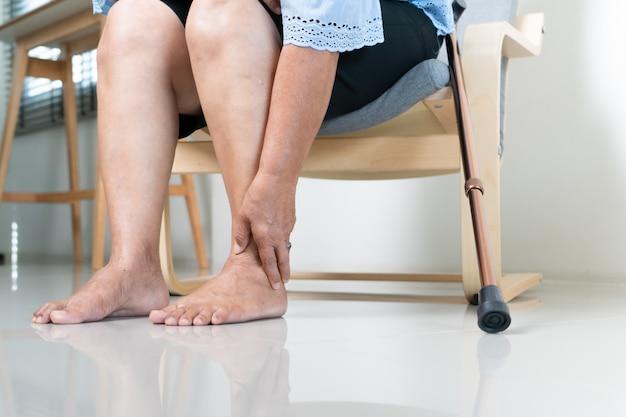 Dor no tornozelo de uma mulher idosa em casa, problema de saúde do conceito sênior