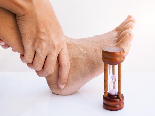 Dor no tornozelo e pés machucados, pé dolorido de asiáticos com relógio de areia ou ampulheta, conceito de tempo e cuidados de saúde de pé.