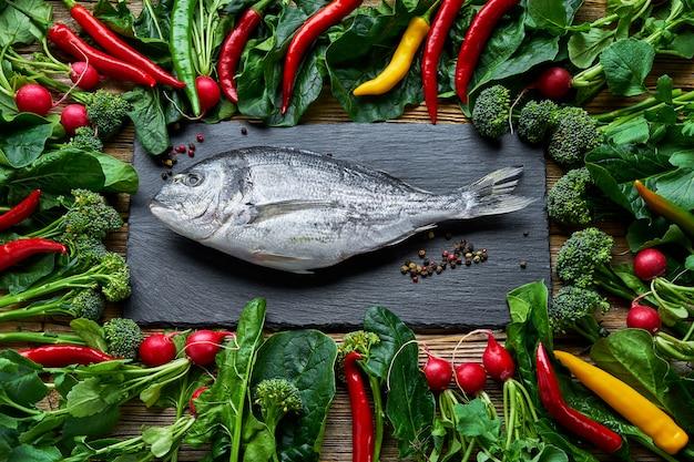 Dorada peixe e vegetais verdes ao redor na mesa de madeira velha
