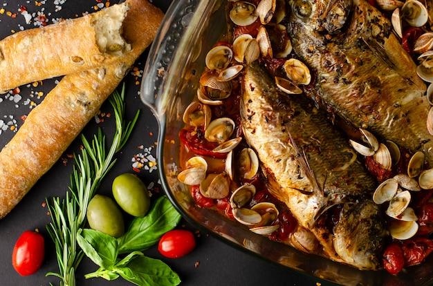 Dorada peixe grelhado com mariscos no prato, pão de azeitona italiana e alecrim em fundo escuro