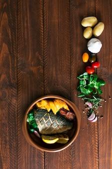 Dorado assado com salada e legumes frescos. vista do topo. mesa de madeira marrom