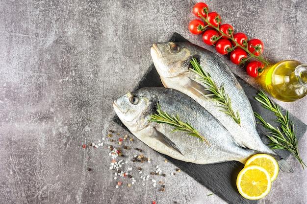 Dorado de peixe cru na tábua de ardósia preta e fundo de concreto cinza com especiarias, tomate, alecrim, azeite e limão. vista superior, camada plana com espaço de cópia para o texto