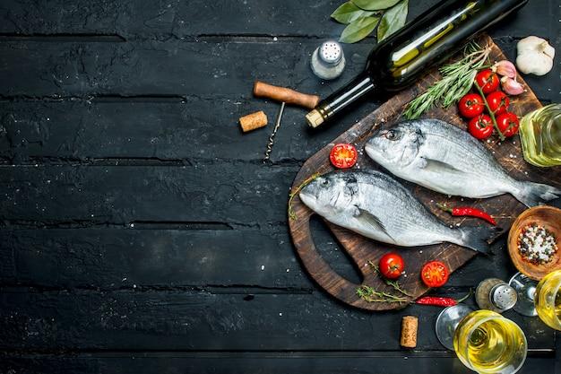 Dorado de peixe do mar cru com ervas, especiarias e uma garrafa de vinho branco. sobre um fundo preto rústico.