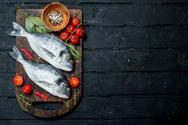 Dorado de peixe do mar cru com tomate, ervas e especiarias. sobre um fundo preto rústico.