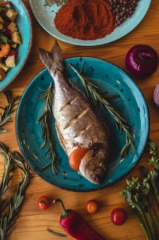 Dorado de peixe fresco. dorado e ingredientes para cozinhar em uma mesa.
