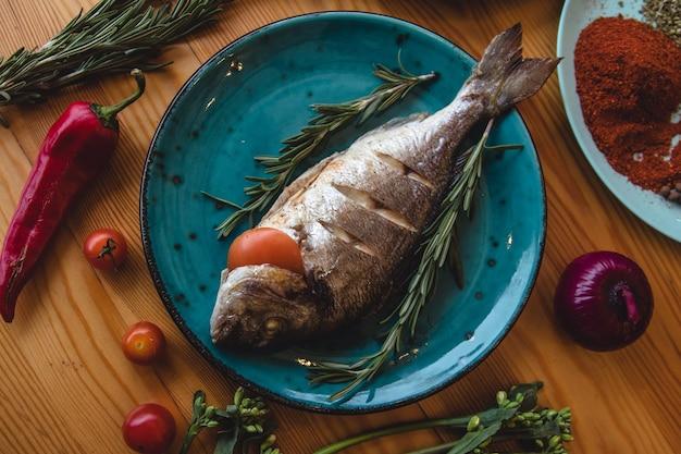 Dorado de peixe fresco. dorado e ingredientes para cozinhar na mesa.
