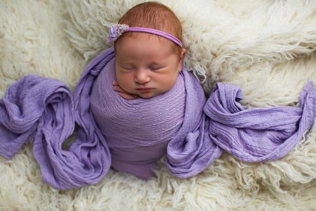 Dormindo, menina recém-nascida de nove dias envolta em um manto roxo.