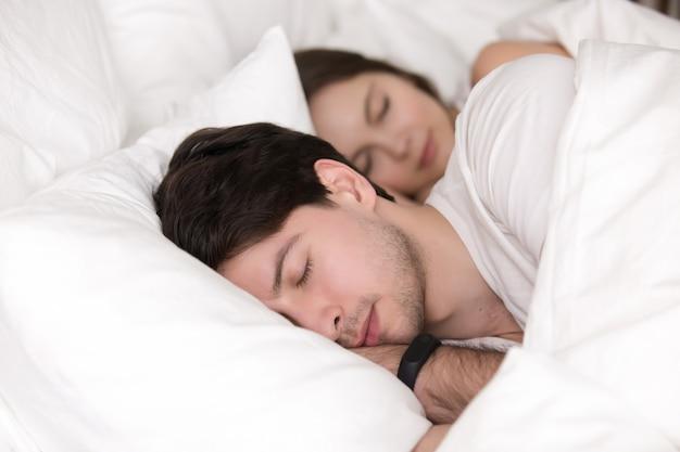 Dormir jovem casal na cama, homem vestindo rastreador relógio inteligente