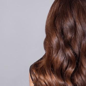 Dorso feminino com cabelo castanho comprido e encaracolado