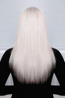 Dorso feminino com cabelo longo, liso e loiro