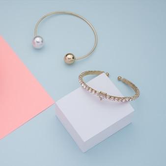 Dourado com diamantes e pulseiras de pérolas na cor azul e rosa de fundo