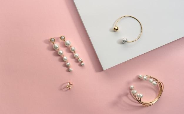 Dourado com pulseiras e brincos de pérolas na superfície branca e rosa