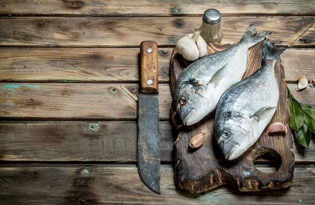 Dourado de peixe do mar cru com ervas e especiarias aromáticas. em uma madeira.