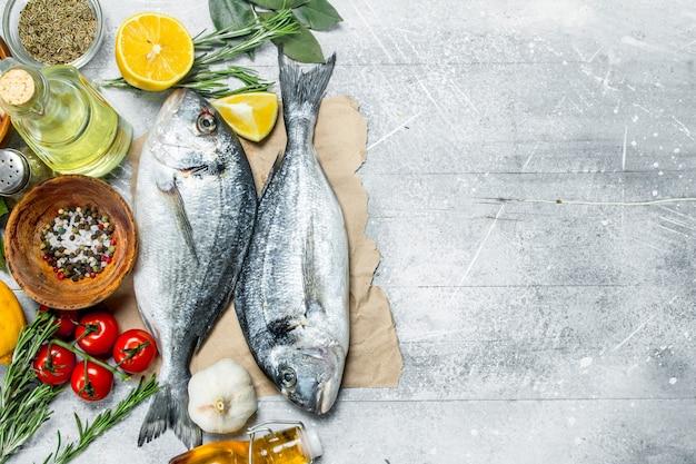 Dourado de peixe do mar cru com limão e especiarias aromáticas. em um rústico.