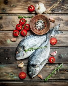 Dourado de peixe do mar cru com tomates, especiarias e ervas. em uma madeira.