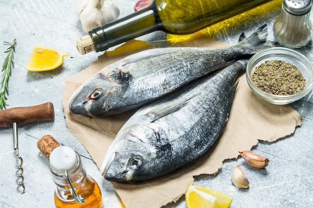 Dourado de peixe do mar cru com vinho branco e especiarias. em um rústico.