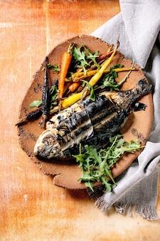 Dourado eviscerado fresco cozido grelhado ou peixe na placa de cerâmica envolto em folhas de bambu servido com ervas, cenouras coloridas, guardanapo branco sobre a superfície de metal laranja. vista superior, configuração plana