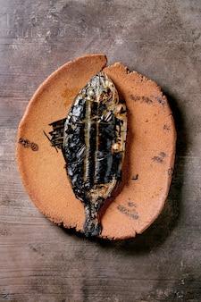 Dourado ou dourado eviscerado fresco cozido grelhado em uma placa de cerâmica envolto em folhas de bambu sobre uma superfície de textura marrom escura. vista superior, configuração plana