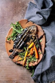 Dourado ou dourado eviscerado fresco cozido grelhado no prato de cerâmica envolto em folhas de bambu servido com ervas, cenouras coloridas, guardanapo azul sobre superfície marrom escura vista superior, configuração plana