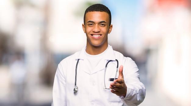 Doutor afro-americano novo do homem que agita as mãos para fechar um bom negócio em ao ar livre
