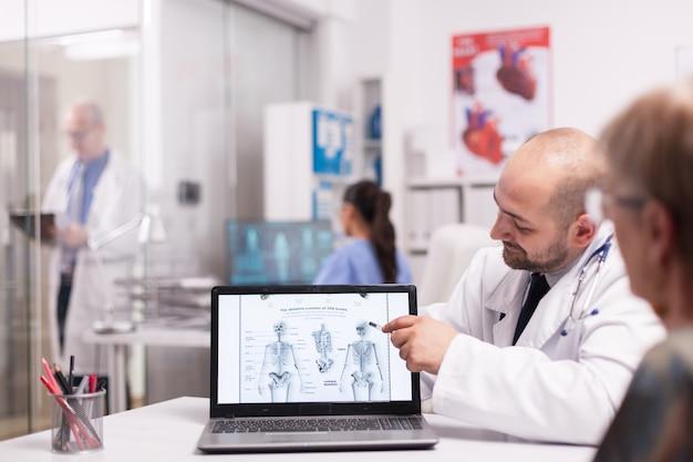 Doutor, apontando para o esqueleto humano no laptop no escritório do hospital durante a consulta da velha antes da cirurgia. médico sênior vestindo jaleco branco tomando notas na área de transferência no corredor da clínica.