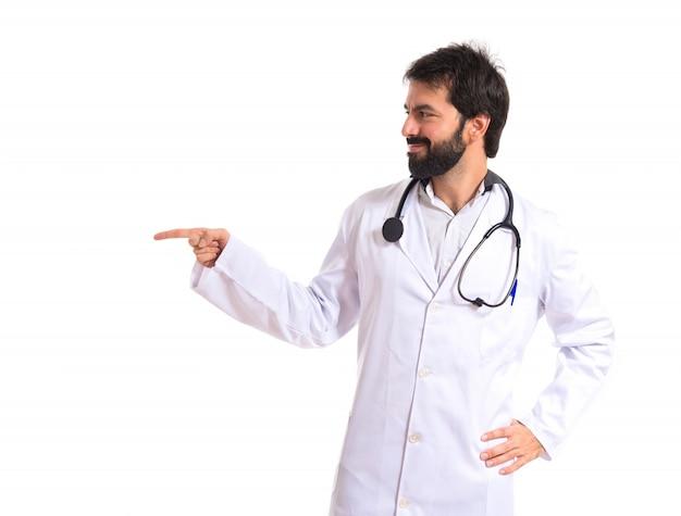 Doutor apontando para o fundo lateral sobre o branco