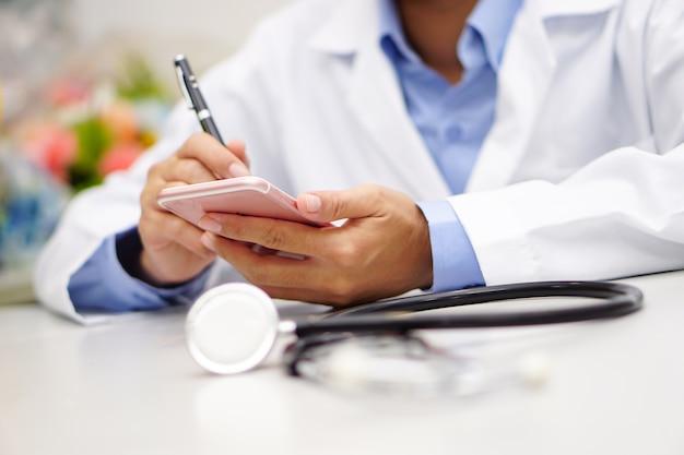 Doutor asiático que guarda o telefone celular para comunicar-se sobre o trabalho no escritório moderno.