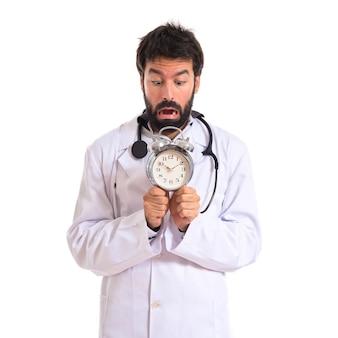 Doutor assustado segurando um relógio