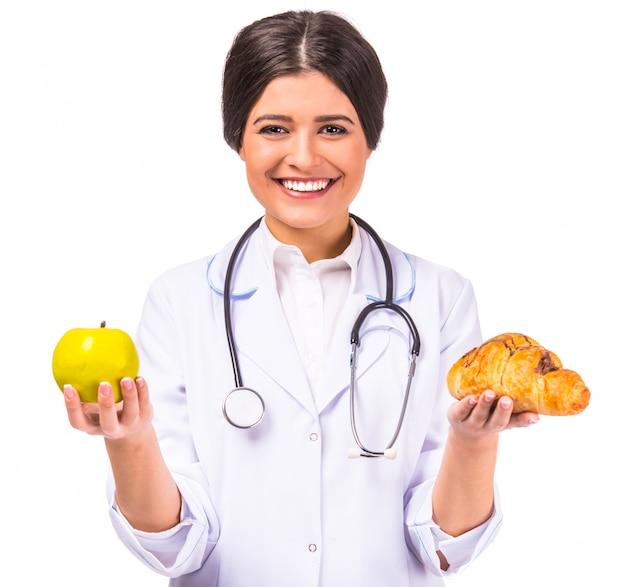 Doutor bonito novo da mulher em um revestimento branco com fruta.