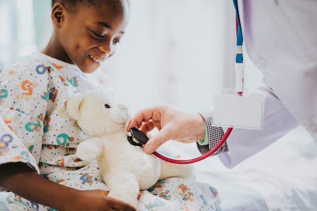 Doutor, brincando, verificando o coração bater de um ursinho de pelúcia