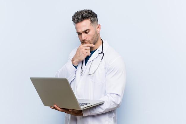 Doutor caucasiano homem segurando o laptop, olhando de soslaio com expressão duvidosa e cética.