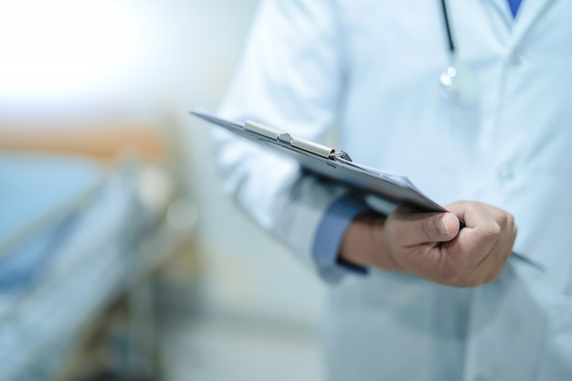 Doutor com a prancheta para o diagnóstico da nota dos pacientes na divisão de hospital de cuidados.