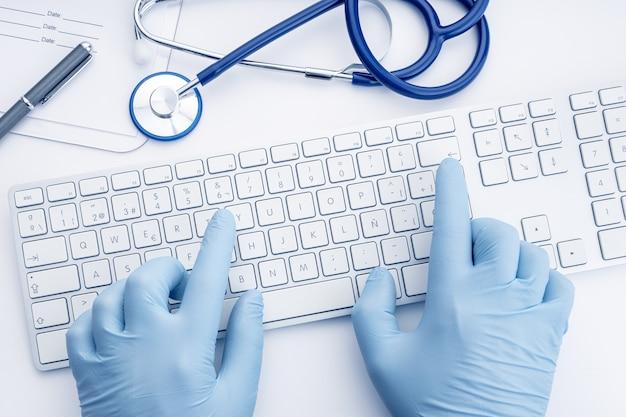 Doutor com as mãos nas luvas, digitando no teclado do computador na mesa branca. fundo de conceito de telemedicina ou tecnologia médica. vista do topo