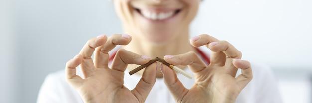 Doutor com cigarro nas mãos e quebrá-lo em clínica closeup. maléficos do conceito de fumar