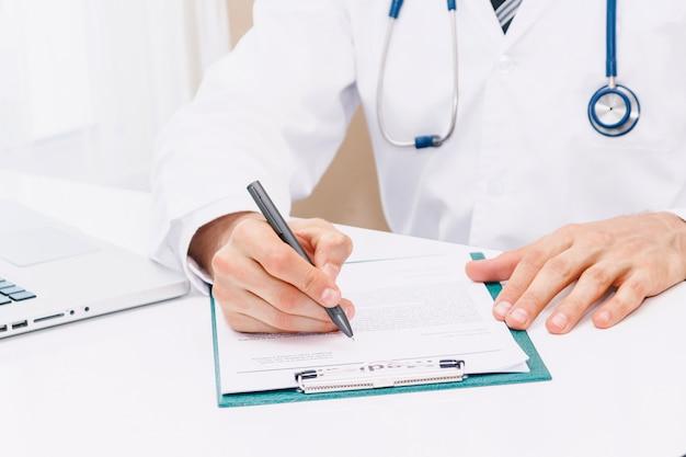Doutor, com, estetoscópio, trabalhando, e, escrita, ligado, paperwork, em, hospital.healthcare, e, medicina