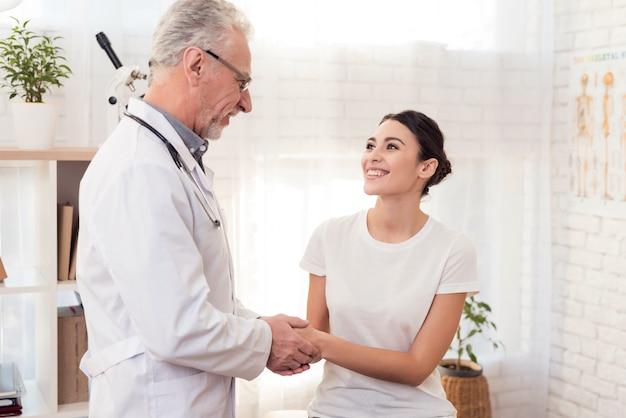 Doutor com o estetoscópio com o paciente fêmea no escritório.