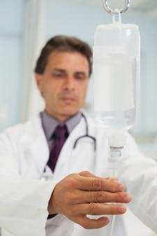 Doutor concentrado conectando o gotejamento